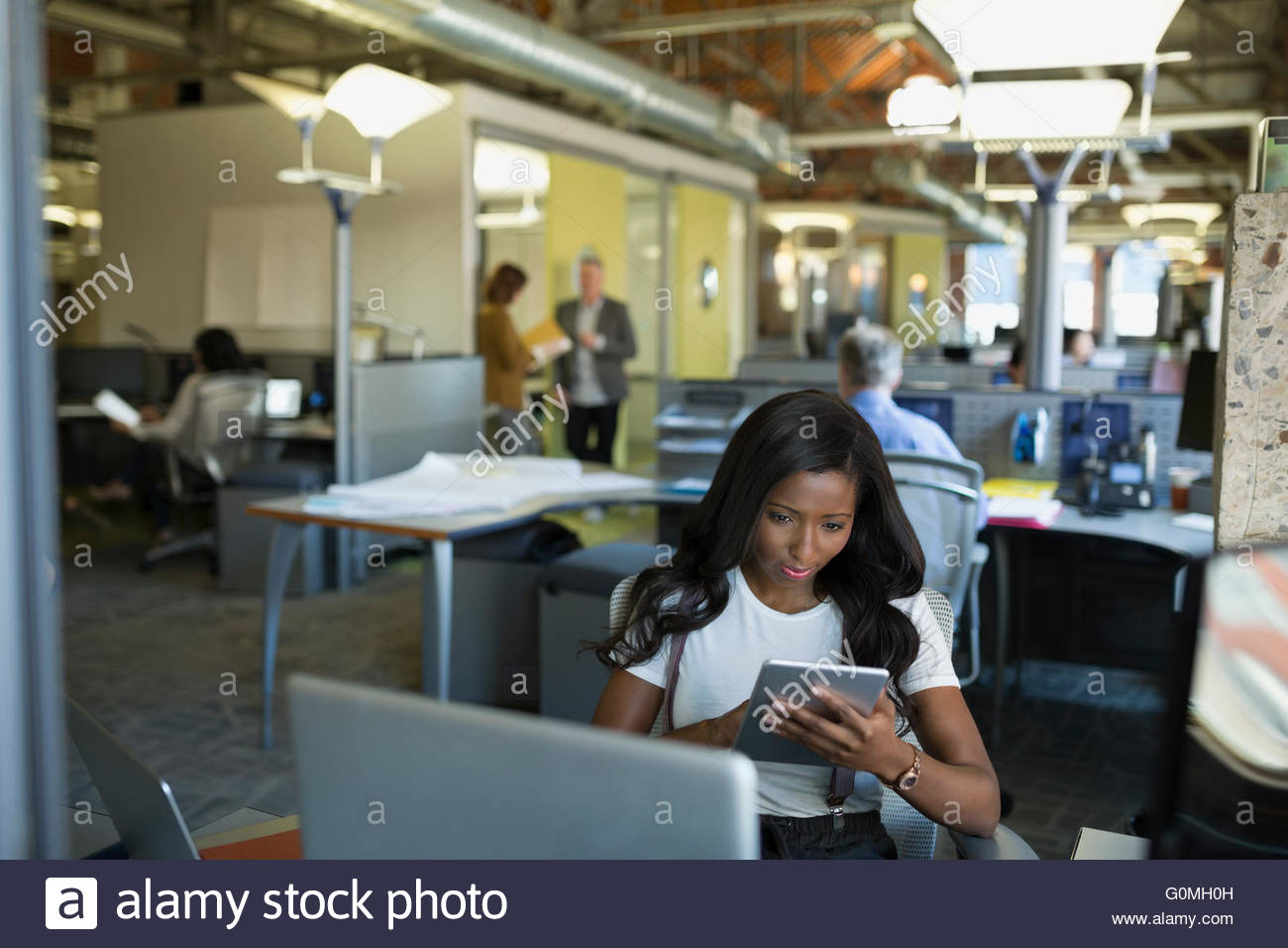 Businesswoman using digital tablet in office - Stock Image