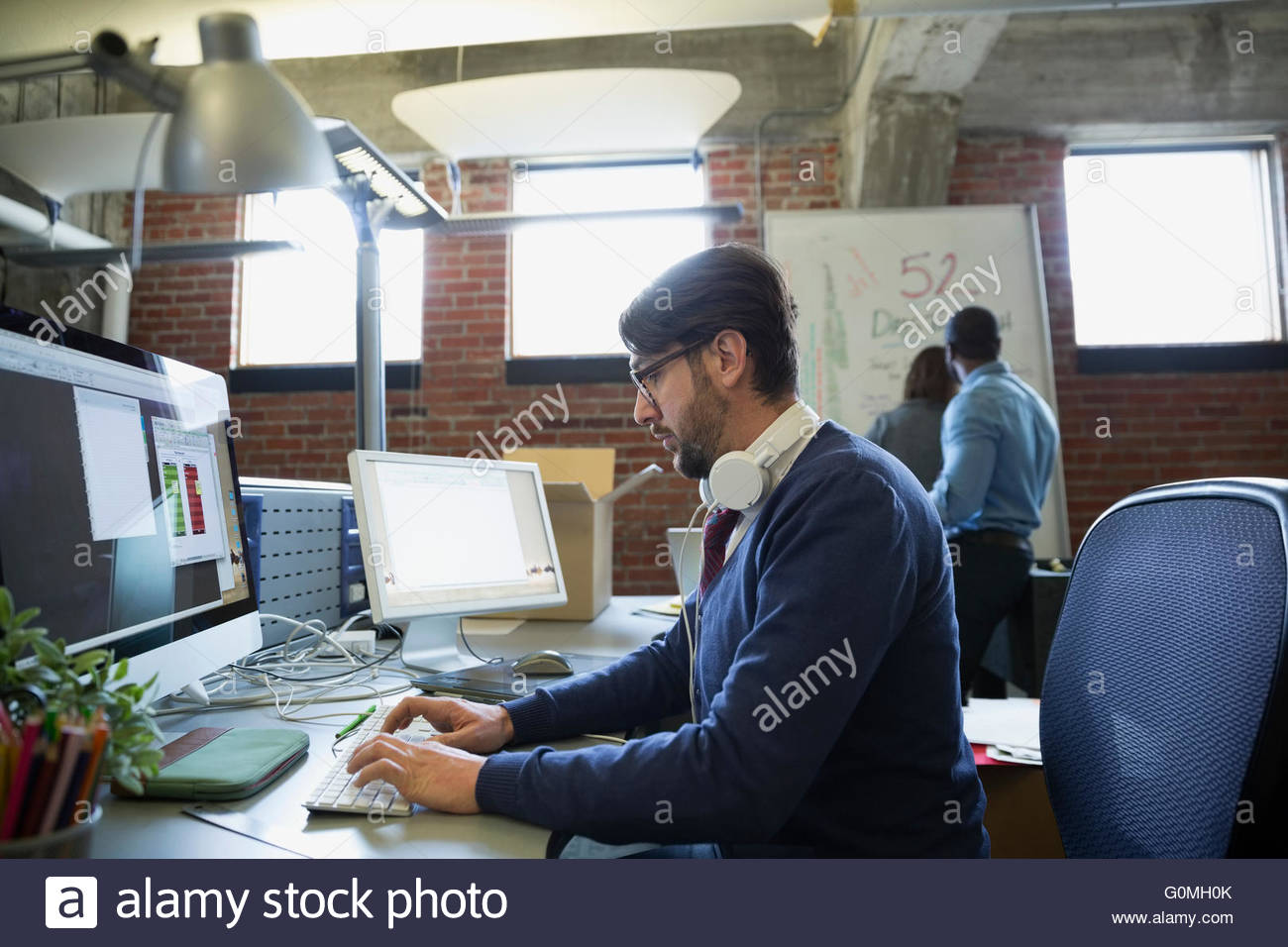 Creative businessman working at computer in office - Stock Image