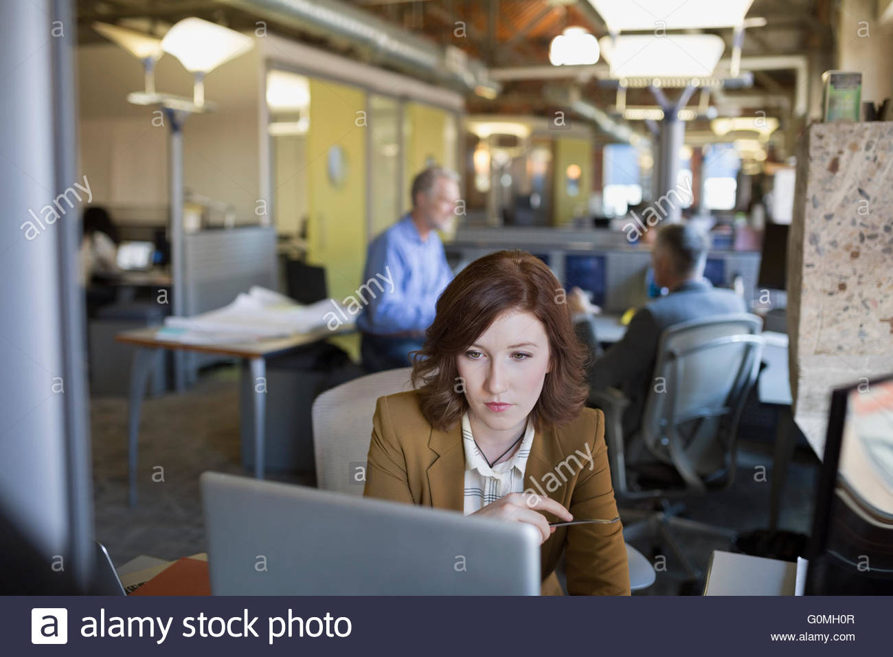 Businesswoman using laptop in office - Stock Image