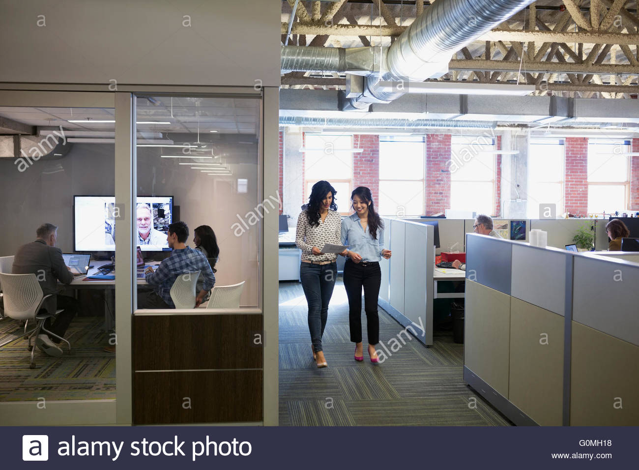 Businesswoman walking by coworkers in video conference - Stock Image