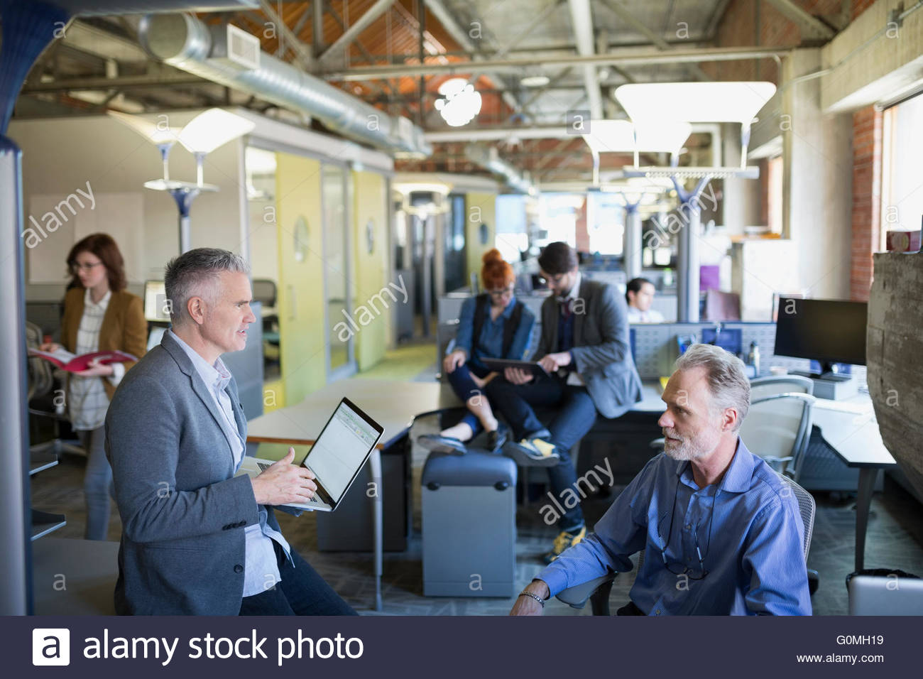 Business people working in open plan office - Stock Image