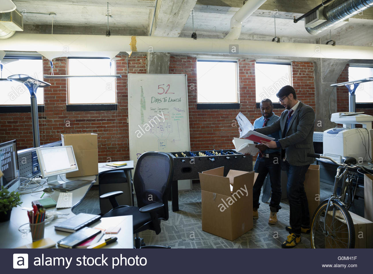 Entrepreneurs discussing paperwork in new office - Stock Image