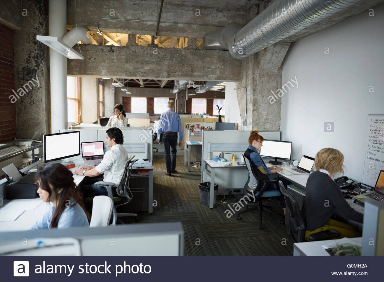 Business people working at desks open plan office - Stock Image