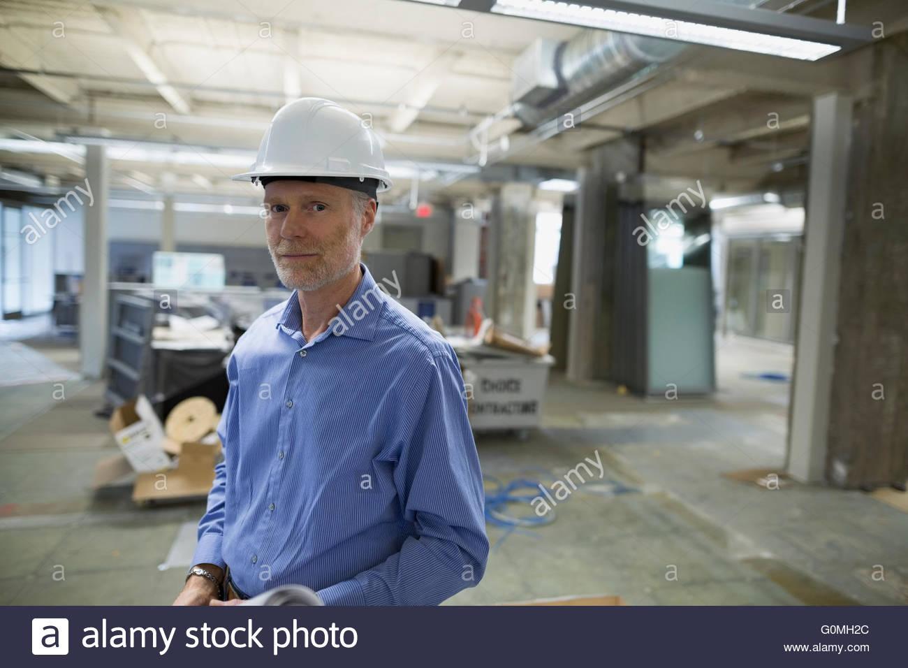Portrait confident architect in hard-hat construction site - Stock Image