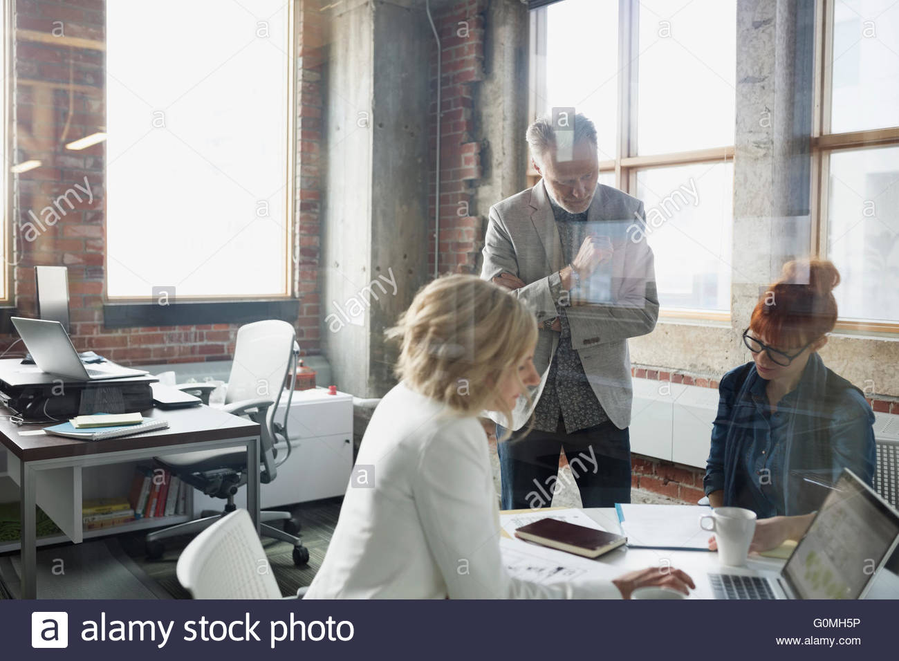 Business people discussing paperwork in meeting - Stock Image