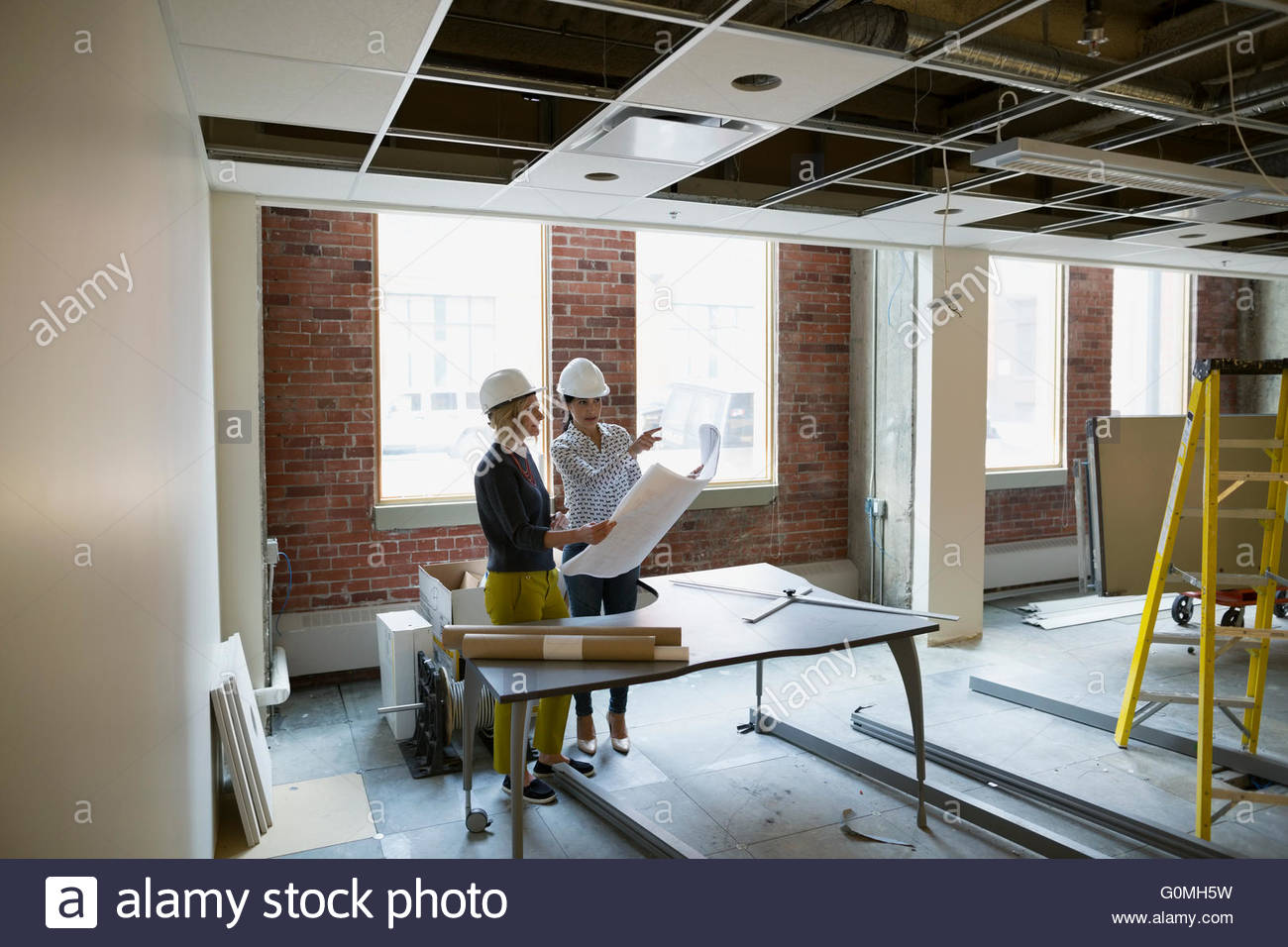 Architect and engineer discussing blueprints office construction site - Stock Image