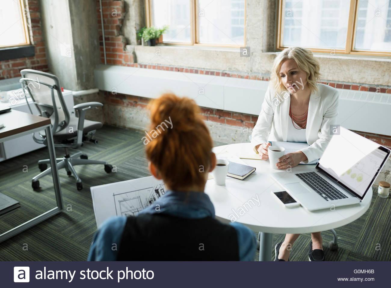 Businesswomen drinking coffee in meeting - Stock Image