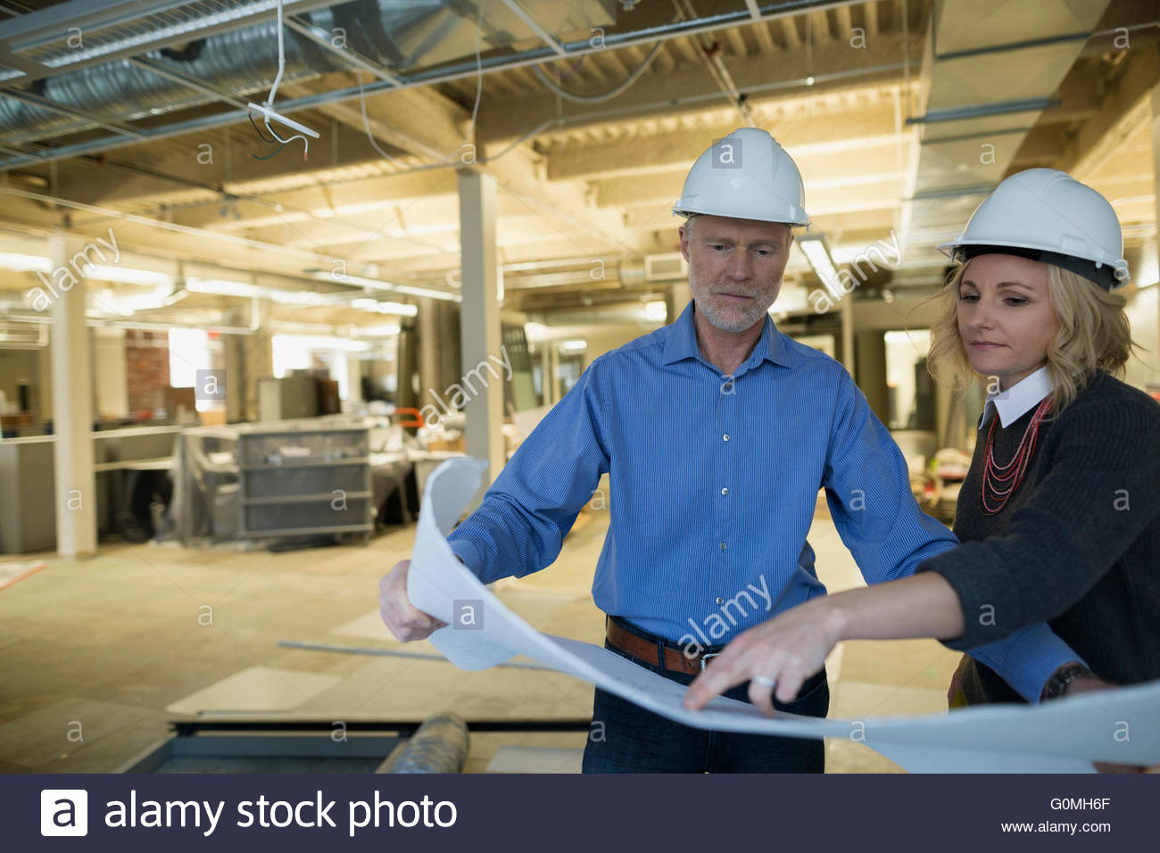 Architect and engineer reviewing blueprints office construction site - Stock Image