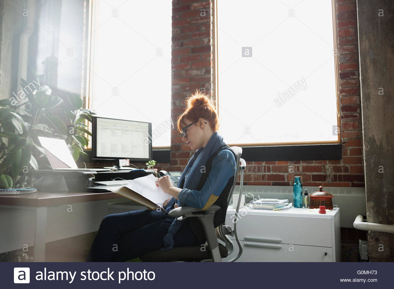 Businesswoman reviewing paperwork at desk in office - Stock Image