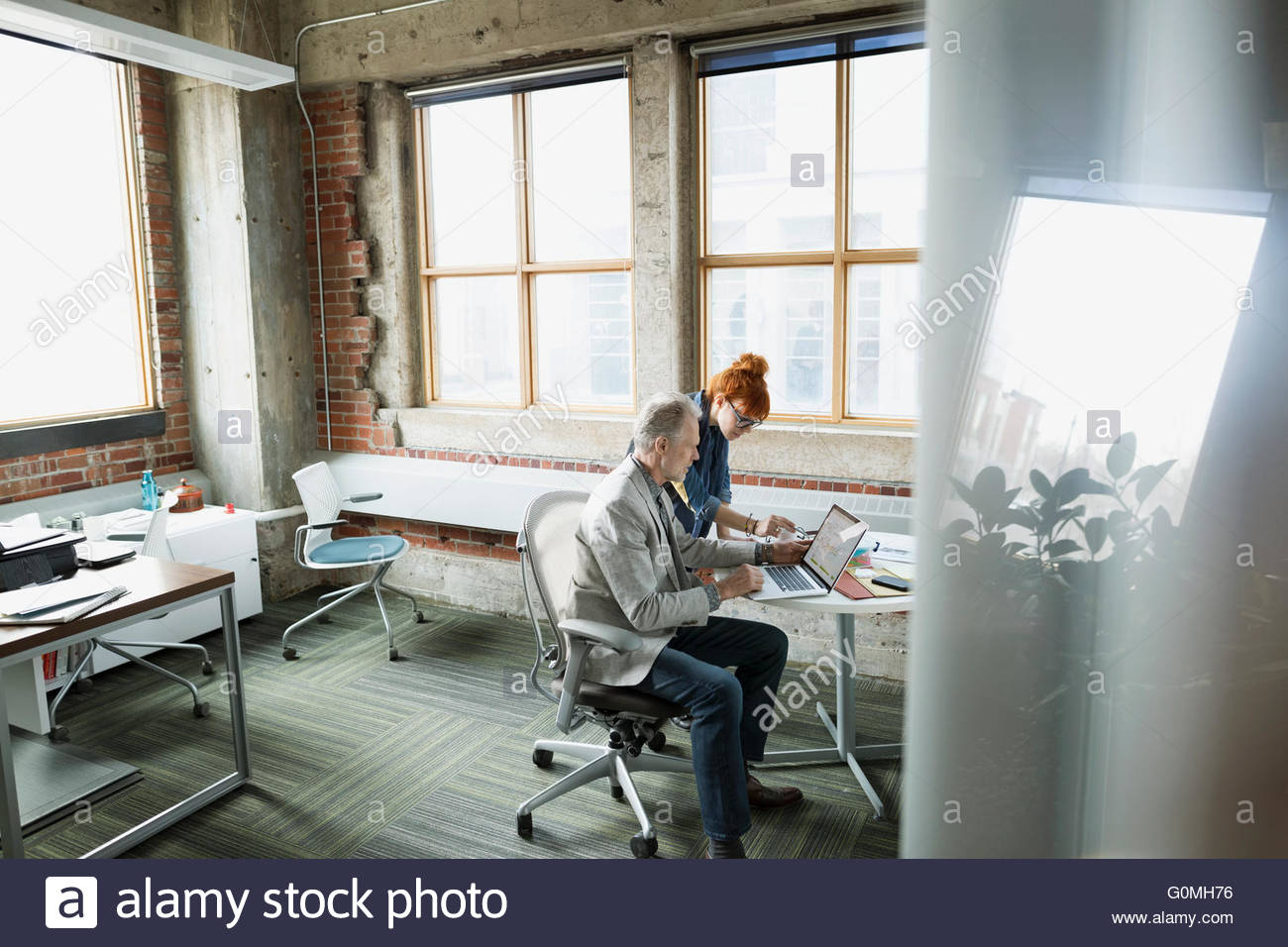 Businessman and businesswoman using laptop in office - Stock Image