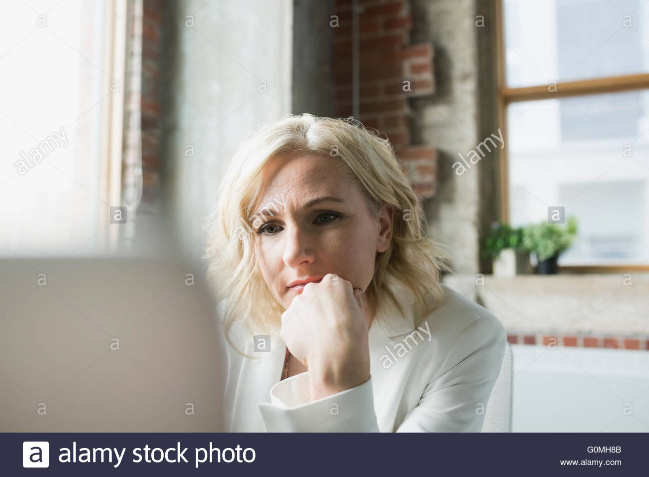 Serious businesswoman using computer in office - Stock Image