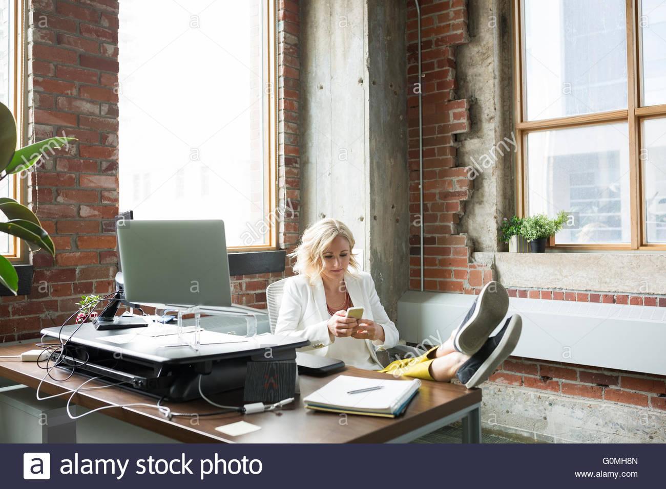 Businesswoman texting with feet up on desk - Stock Image