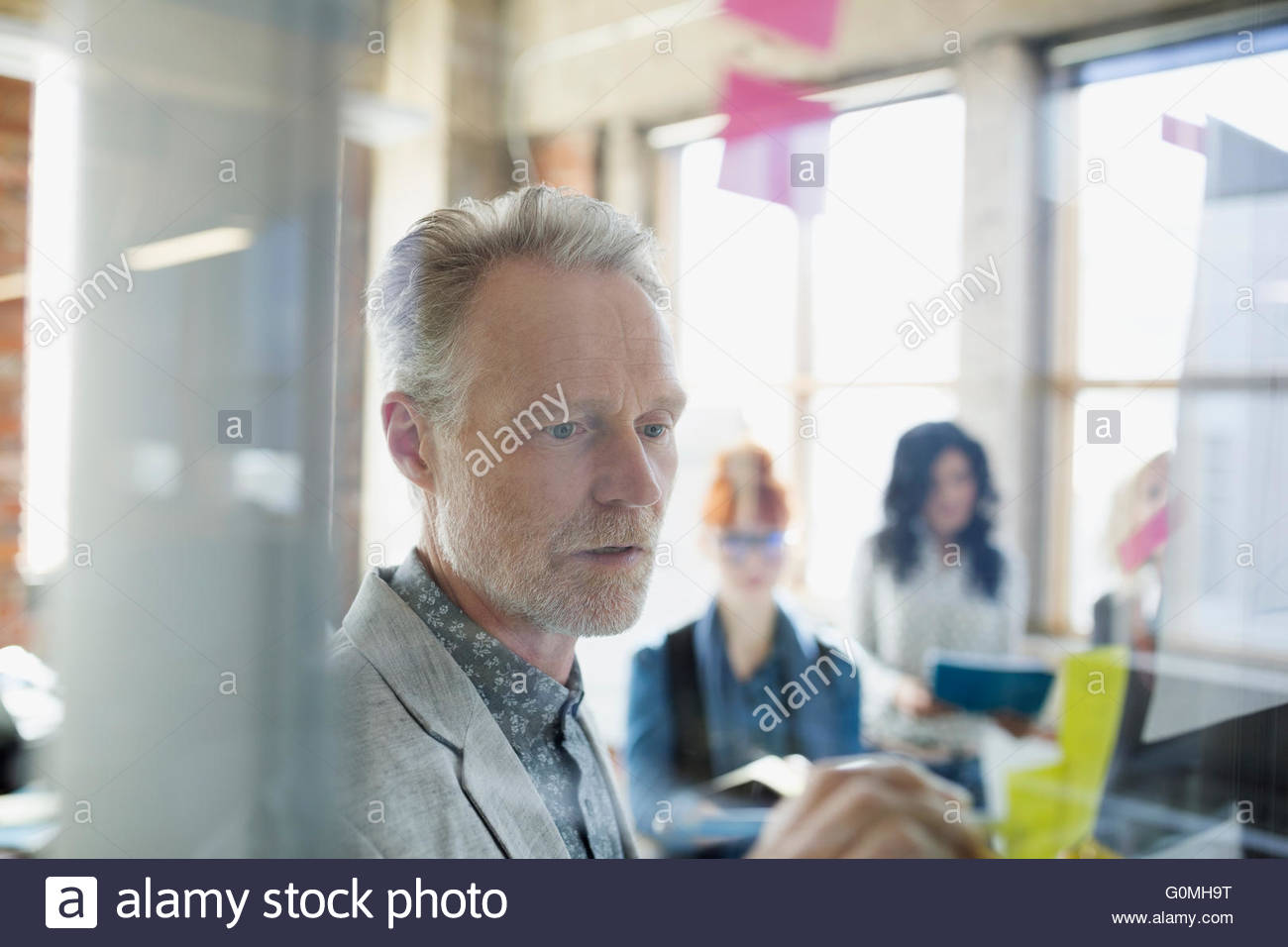 Businessman writing on adhesive note on office glass - Stock Image