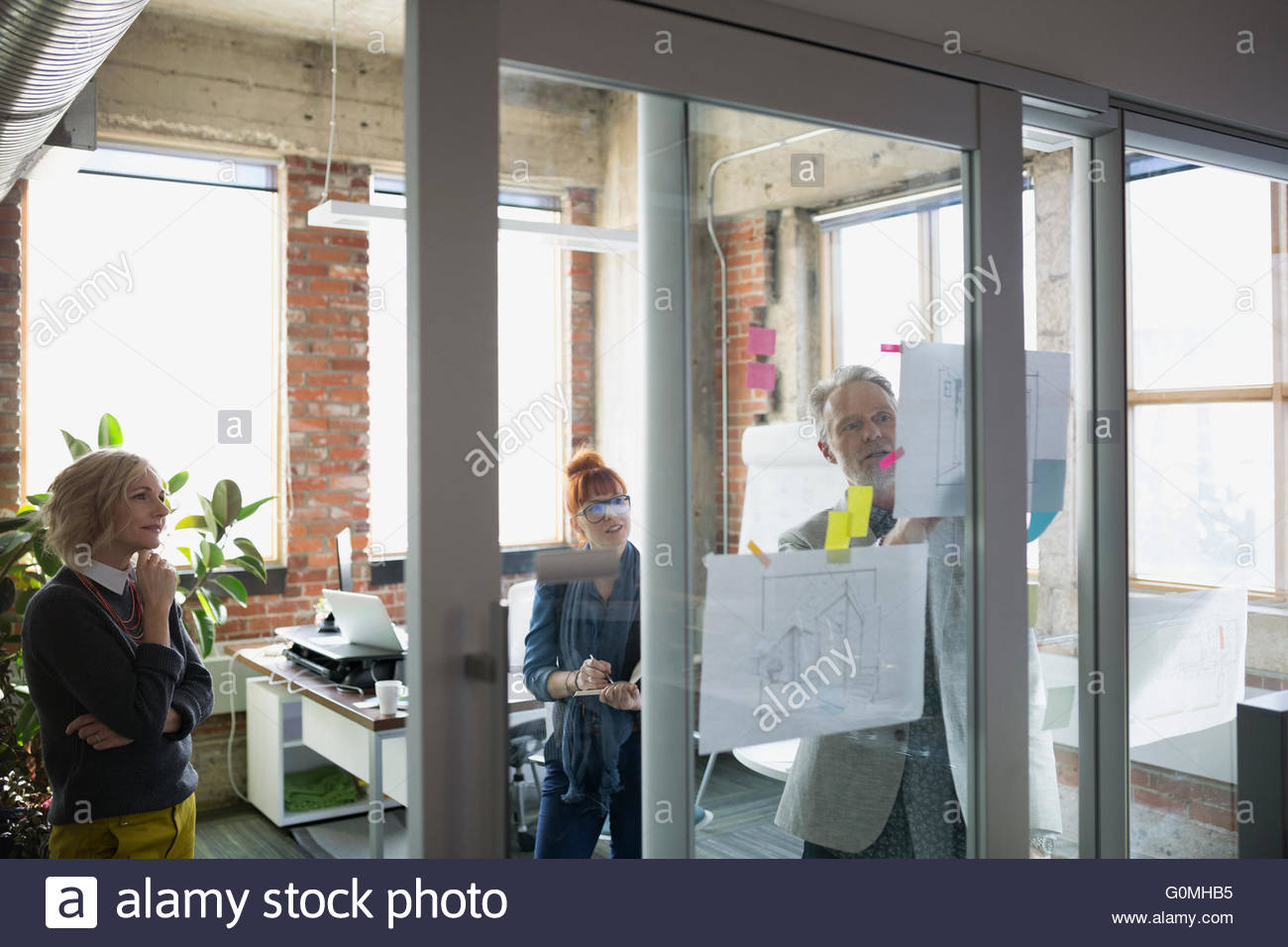 Architects discussing blueprints hanging on office glass - Stock Image
