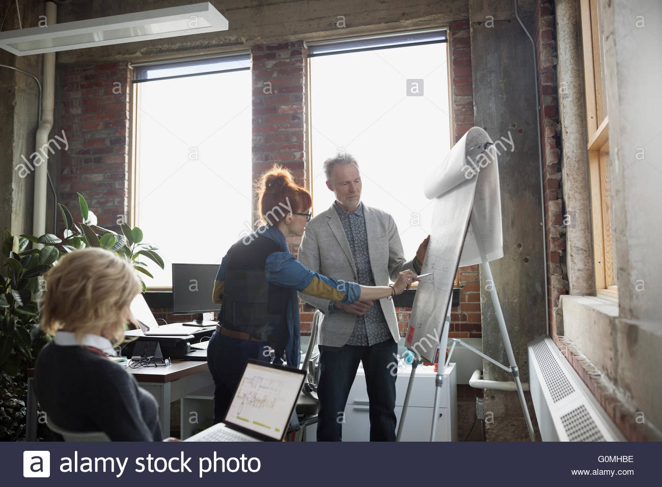 Business people brainstorming at flipchart in office - Stock Image