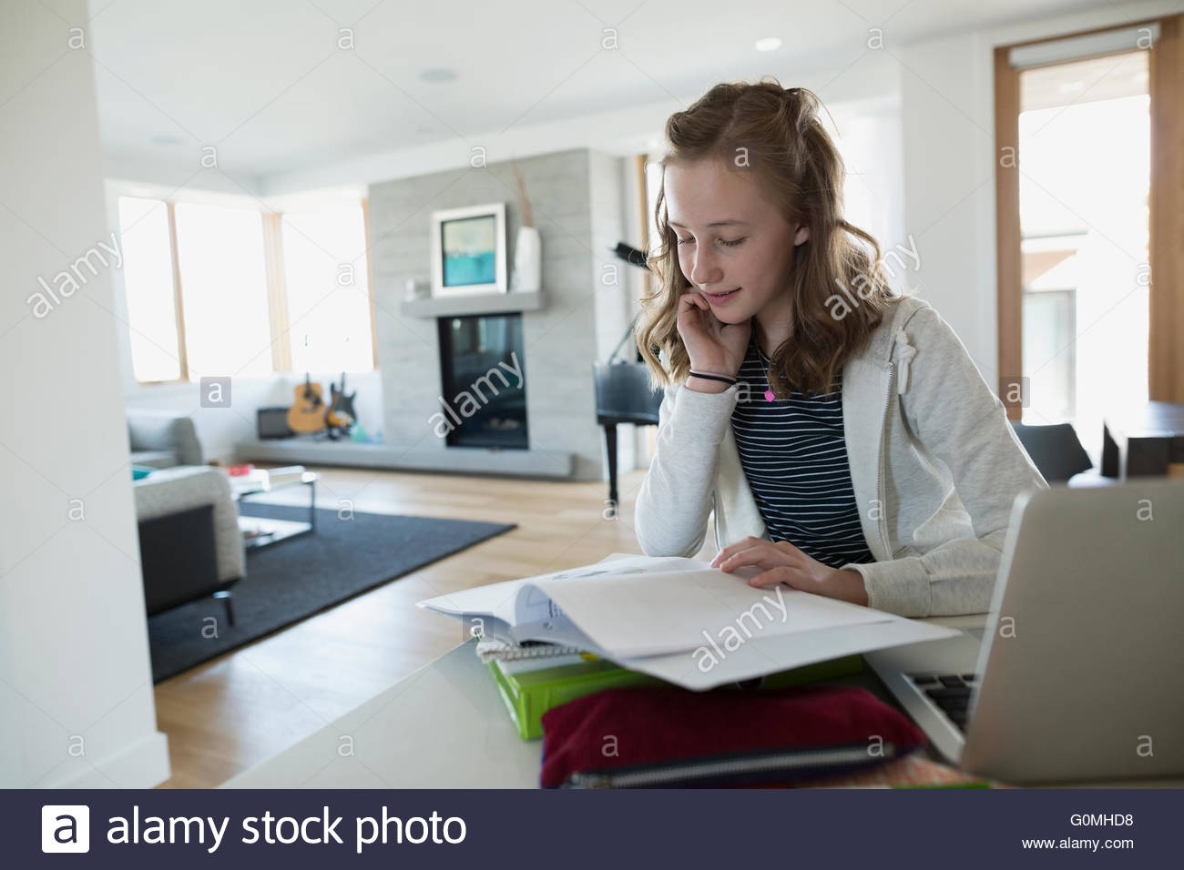 Girl looking at notebook doing homework kitchen counter - Stock Image