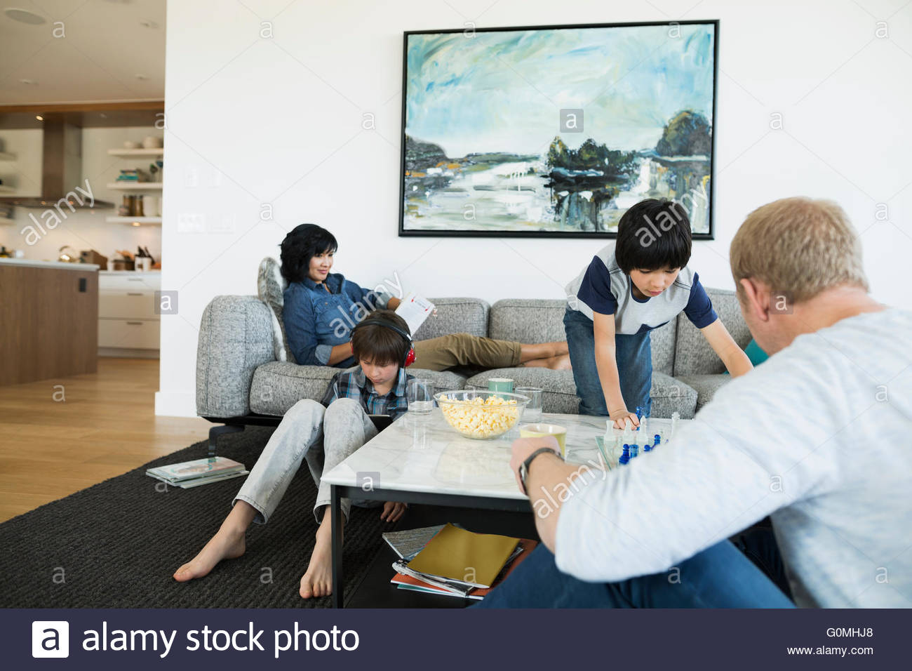 Family relaxing and playing chess in living room - Stock Image