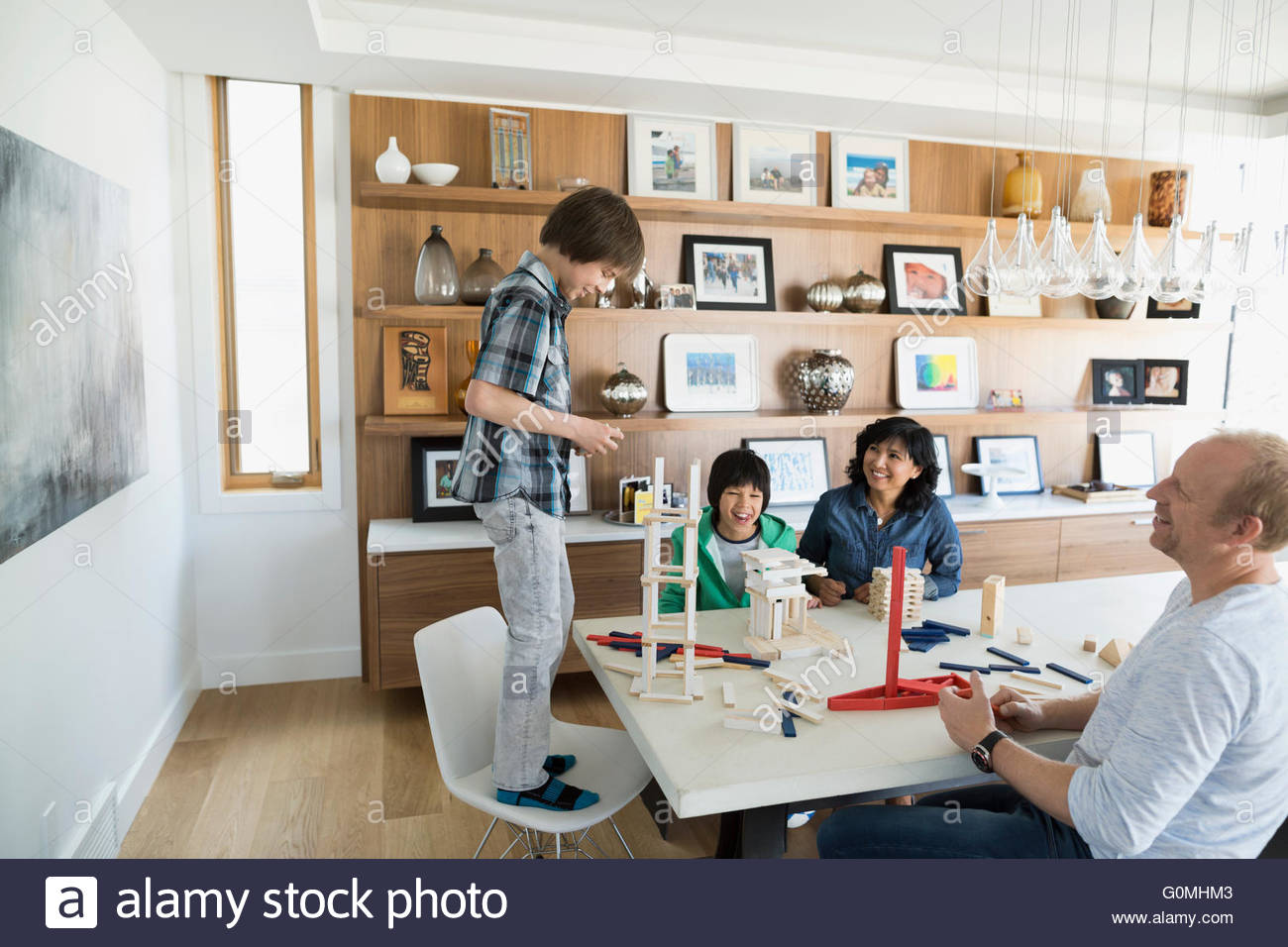 Family playing with building clocks at dining table - Stock Image