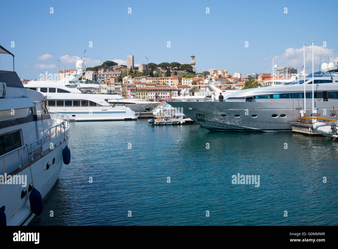 Luxury yachts moored at Cannes, France. The old town of Le Suquet is in the background. - Stock Image