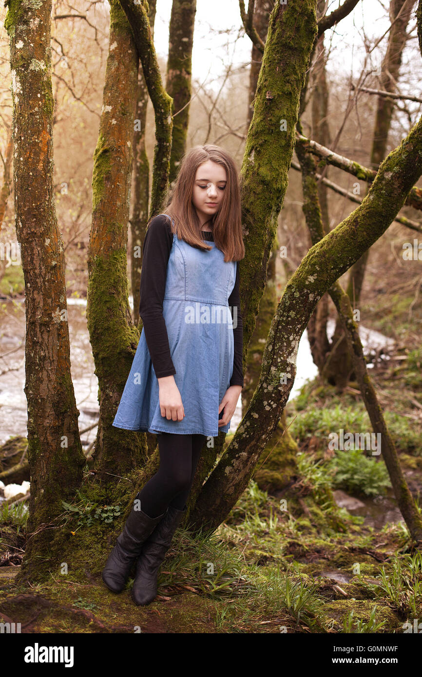 Portrait Of Pretty Child Girl Leaning To A Tree Trunk In
