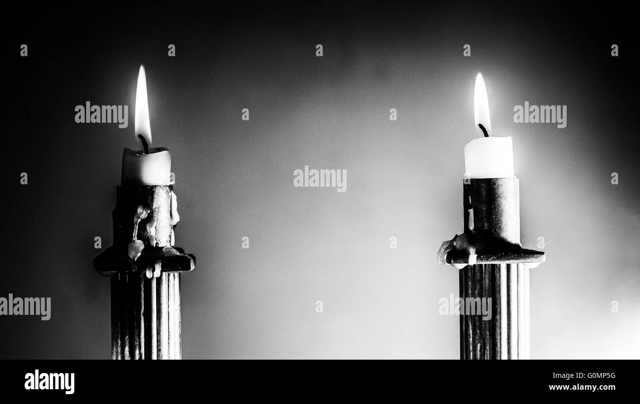 2 Burning candles in Empire Style candle holders in black and white hard contrast - Stock Image