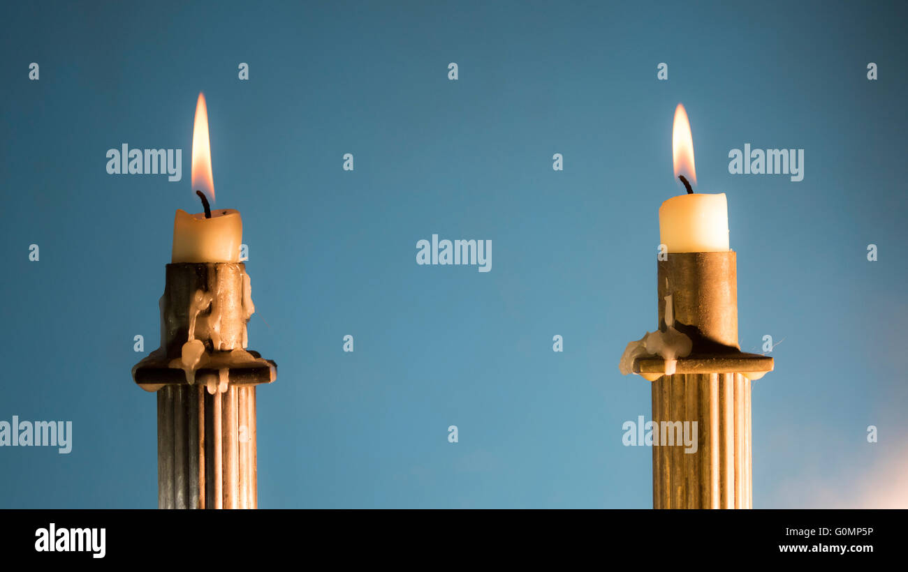 2 Burning candles in Empire Style candle holders in color hard focus - Stock Image