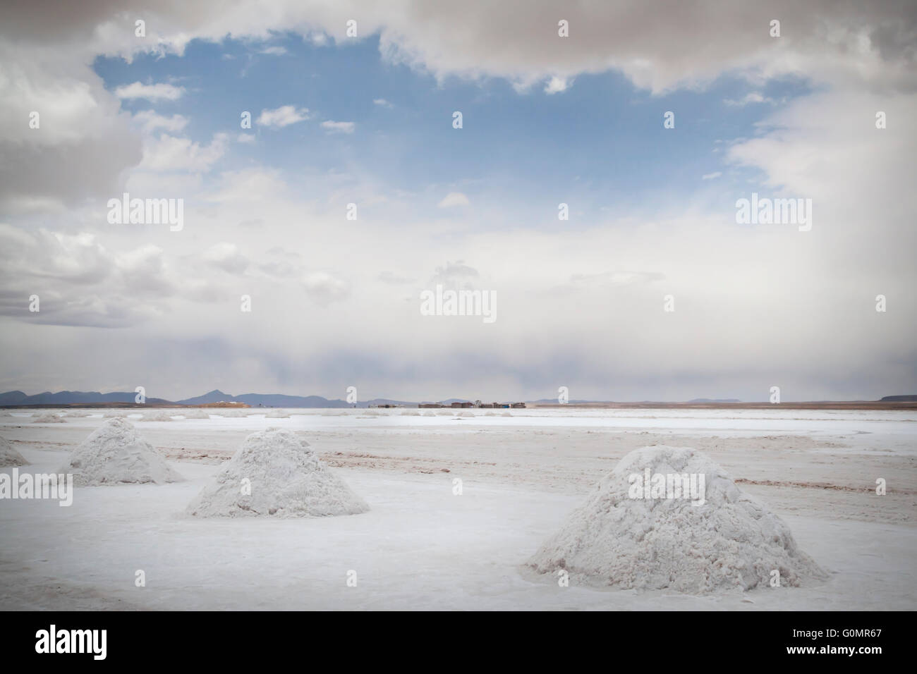 A break in the clouds shows blue sky above the Bolivian salt plains at Salar de Uyuni - Stock Image