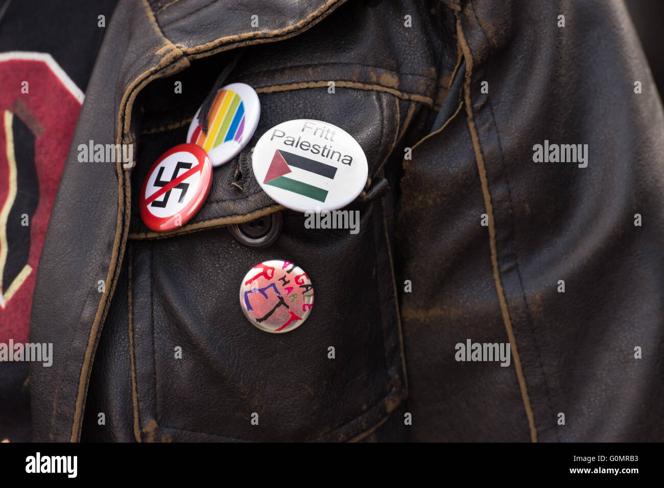 An activist wears a pin saying 'Free Palestine' in Norwegian among anti-fascist and LGBTQ symbols during - Stock Image