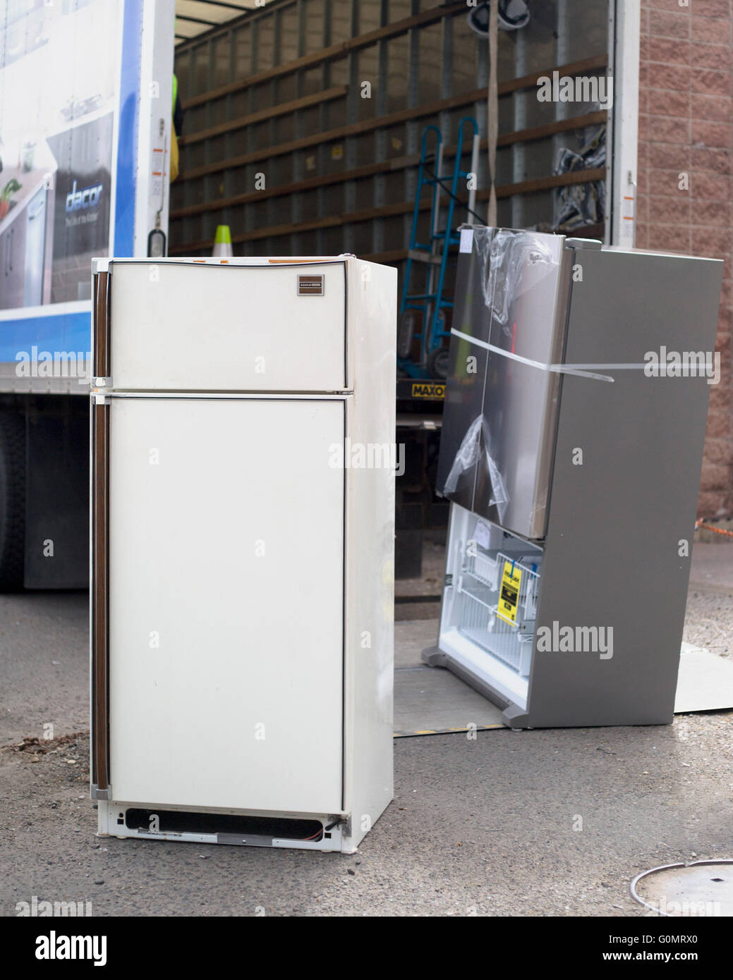 Decades-old refrigerator (front) being hauled away for proper disposal and replaced by a new, more energy efficient - Stock Image