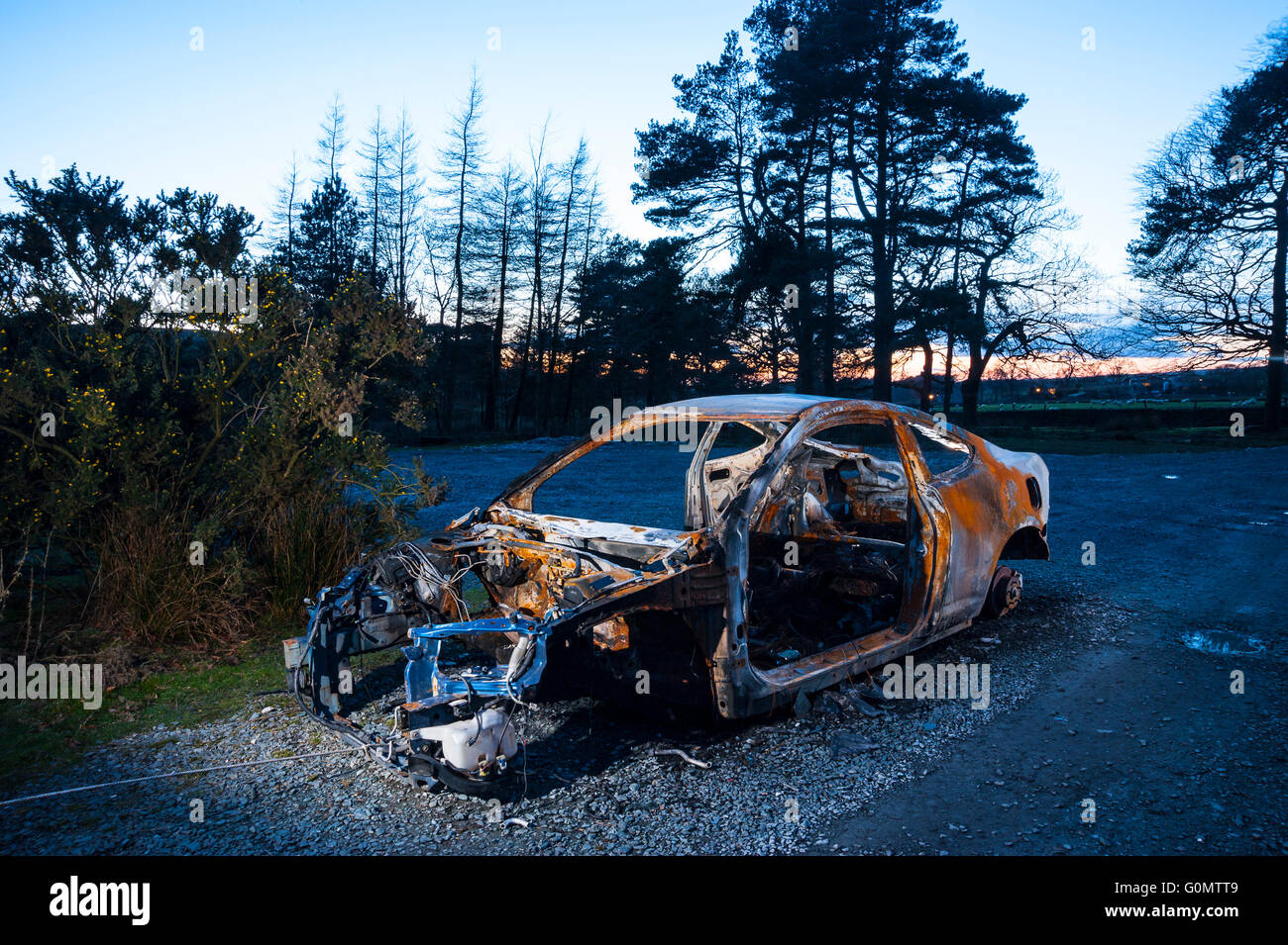 Burned-out car at remote location in Forest of Bowland Lancashire - Stock Image