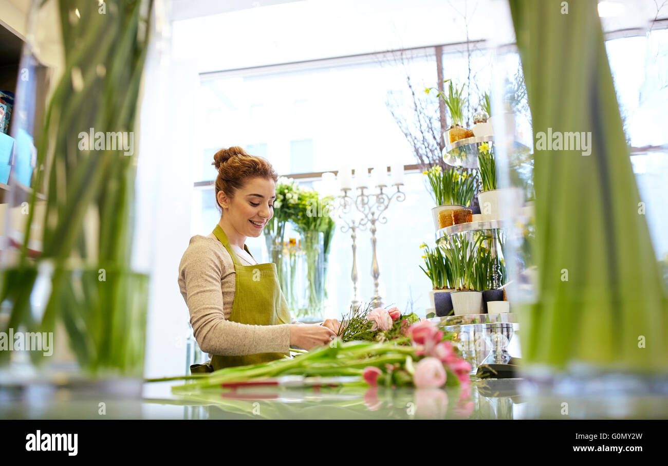 smiling florist woman making bunch at flower shop - Stock Image