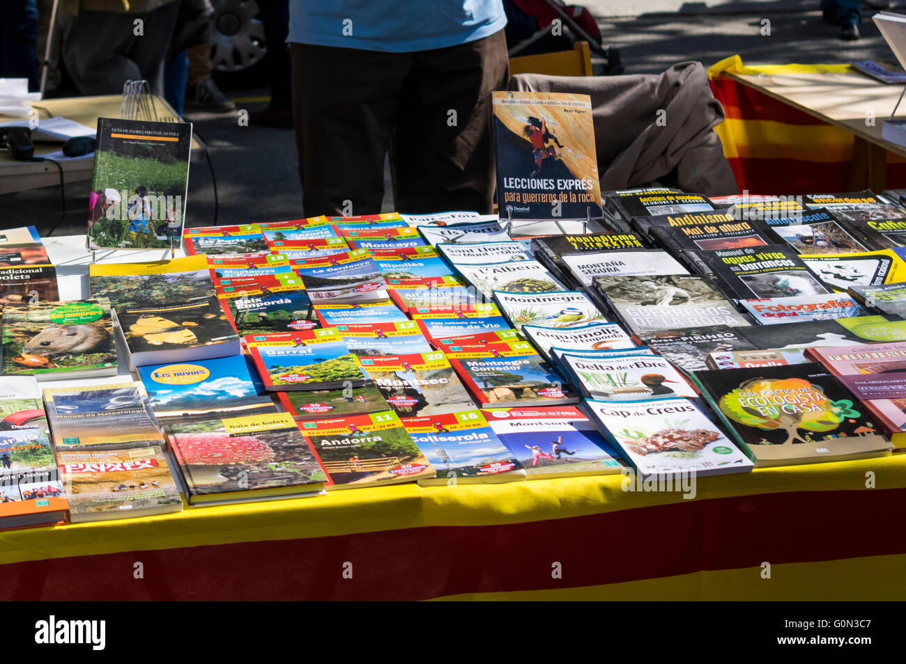 Books for sale at an outdoors booth on Diada de Sant Jordi (Saint George's day), 23 April, in Barcelona, Catalonia. - Stock Image