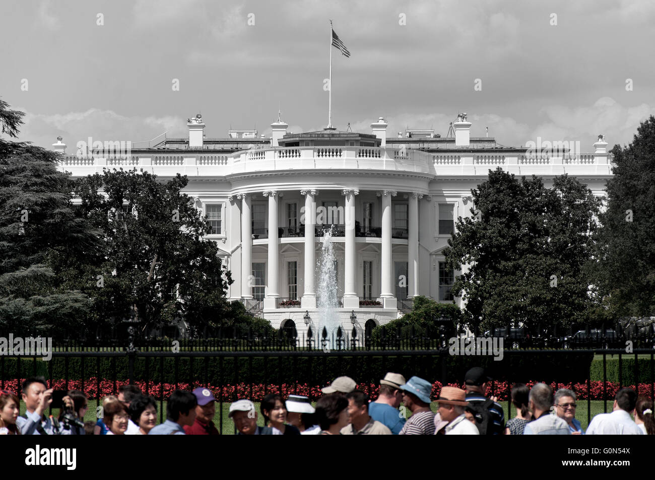 The White House in black and white with crowed in color. - Stock Image