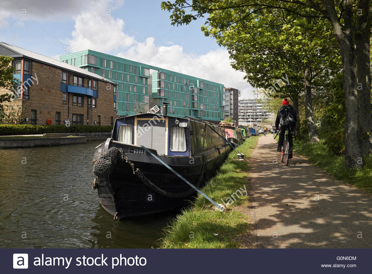Cyclist on the Regents Canal towpath passing moored houseboats near Mile End Lock: London. - Stock Image