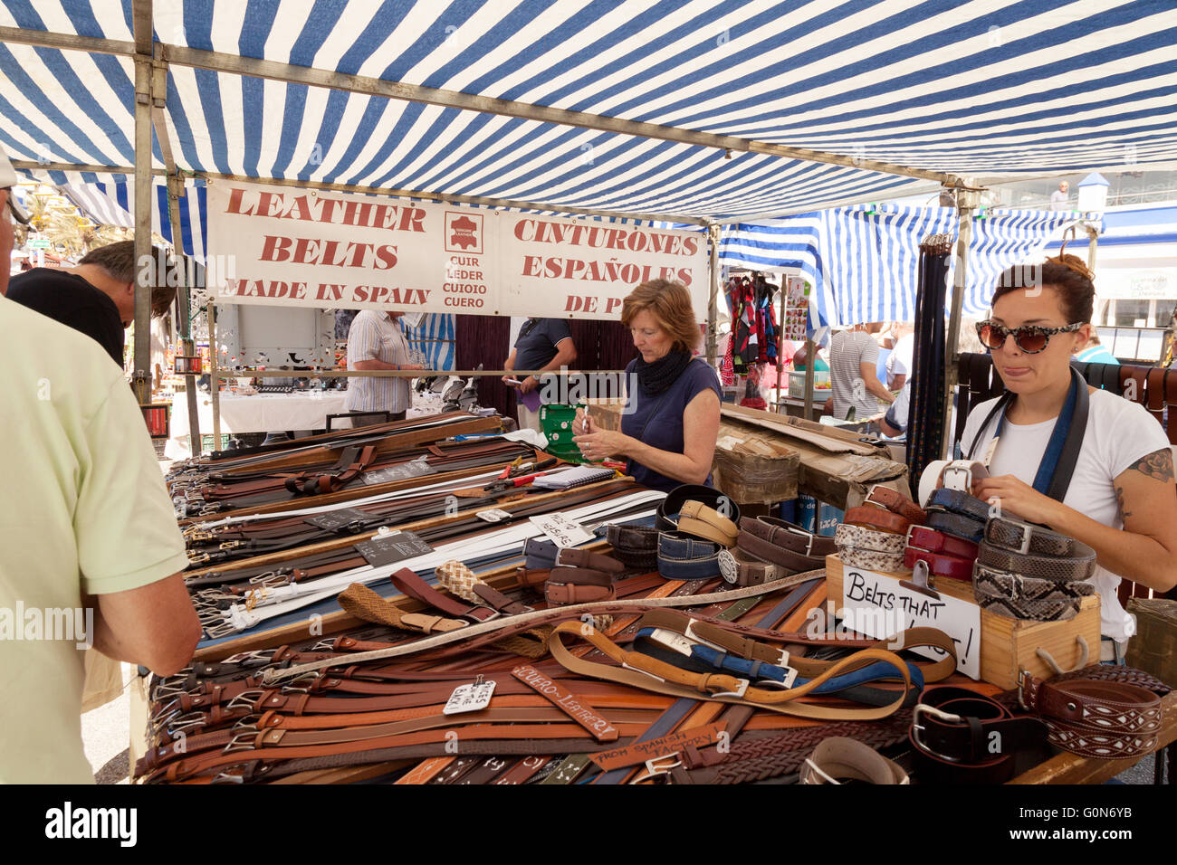 Leather belts stall and stallholder selling to shoppers, Estepona Market, Estepona, Andalusia, Spain Europe - Stock Image