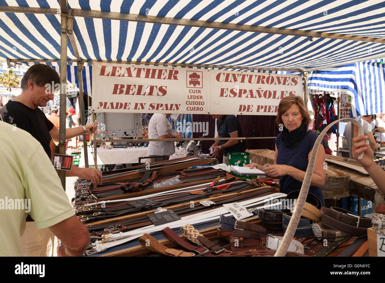 People buying leather belts at a belt stall, Estepona market, Estepona, Costa del Sol, Andalusia, Spain - Stock Image