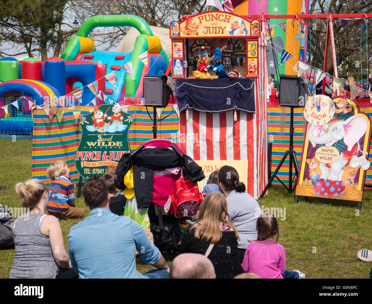 People watching a traditional Punch and Judy puppet show at a summer fair Stock Photo