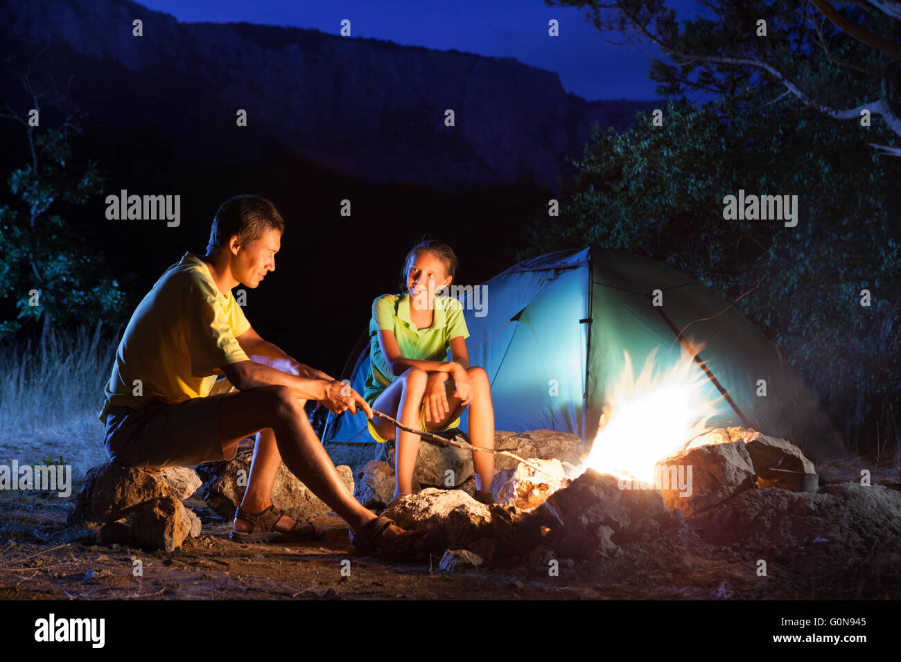 Camping with campfire at night - Stock Image