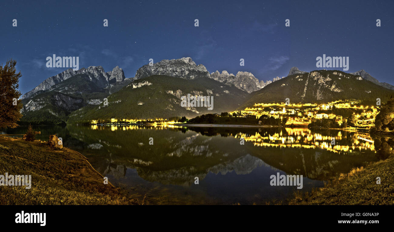 Night landscape of Molveno lake and Dolomiti di Brenta Group in a quiet summer evening with starry sky in the background. - Stock Image