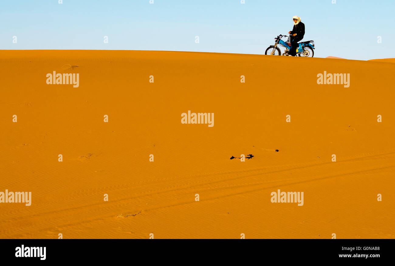 A berber on his motorcycle in the Erg Chebbi sand dunes in Merzouga - Stock Image