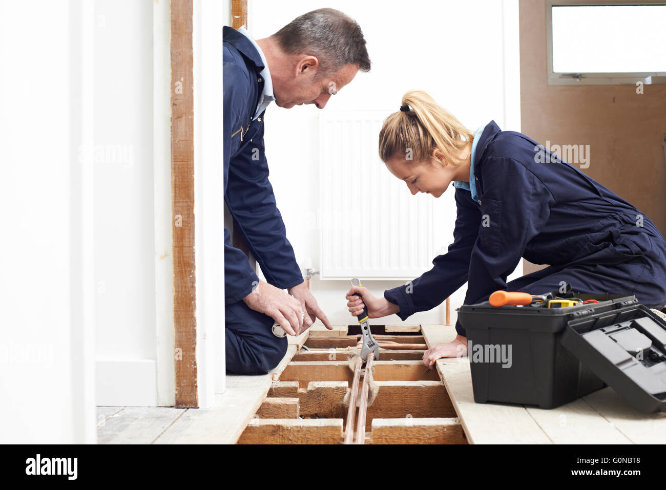 Plumber And Apprentice Fitting Central Heating - Stock Image