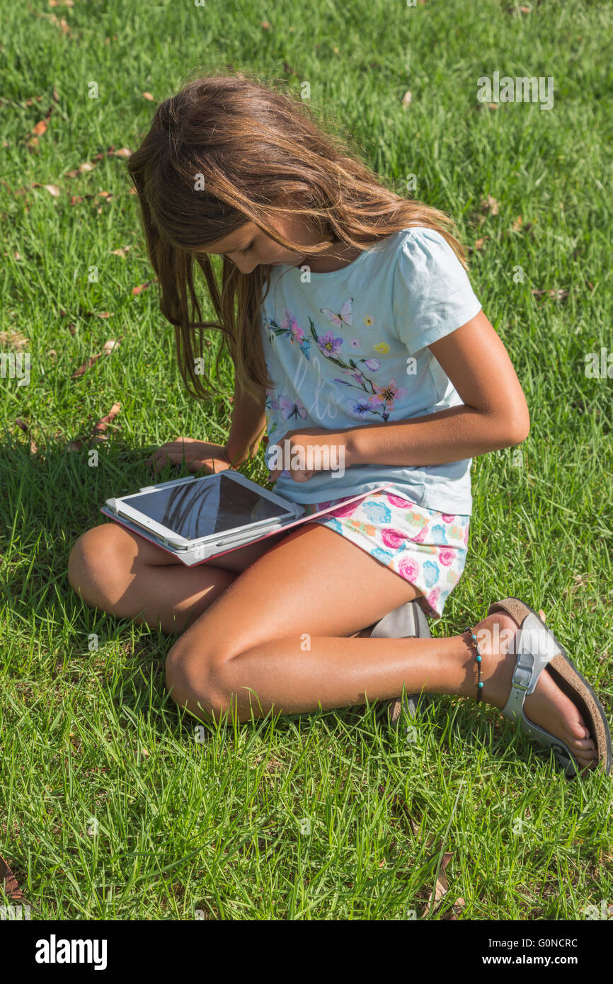 Seven year old girl sitting on grass operating a tablet. - Stock Image