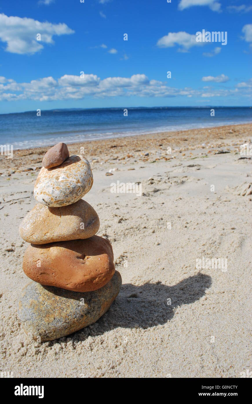 smooth zen like stones stacked in the sand on Bournemouth beach - Stock Image