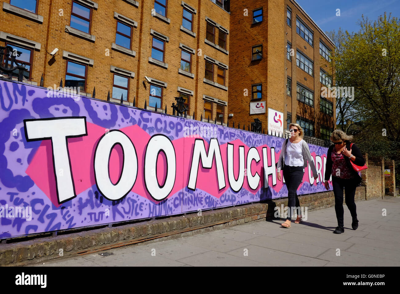 two women walking pass wall art  'TOO MUCH INFORMATION' in London - Stock Image