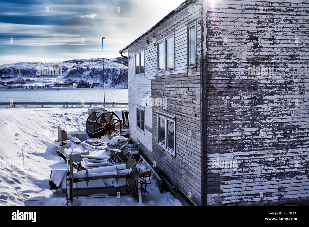 Weathered house covered by snow in front of the norwegian sea Stock Photo
