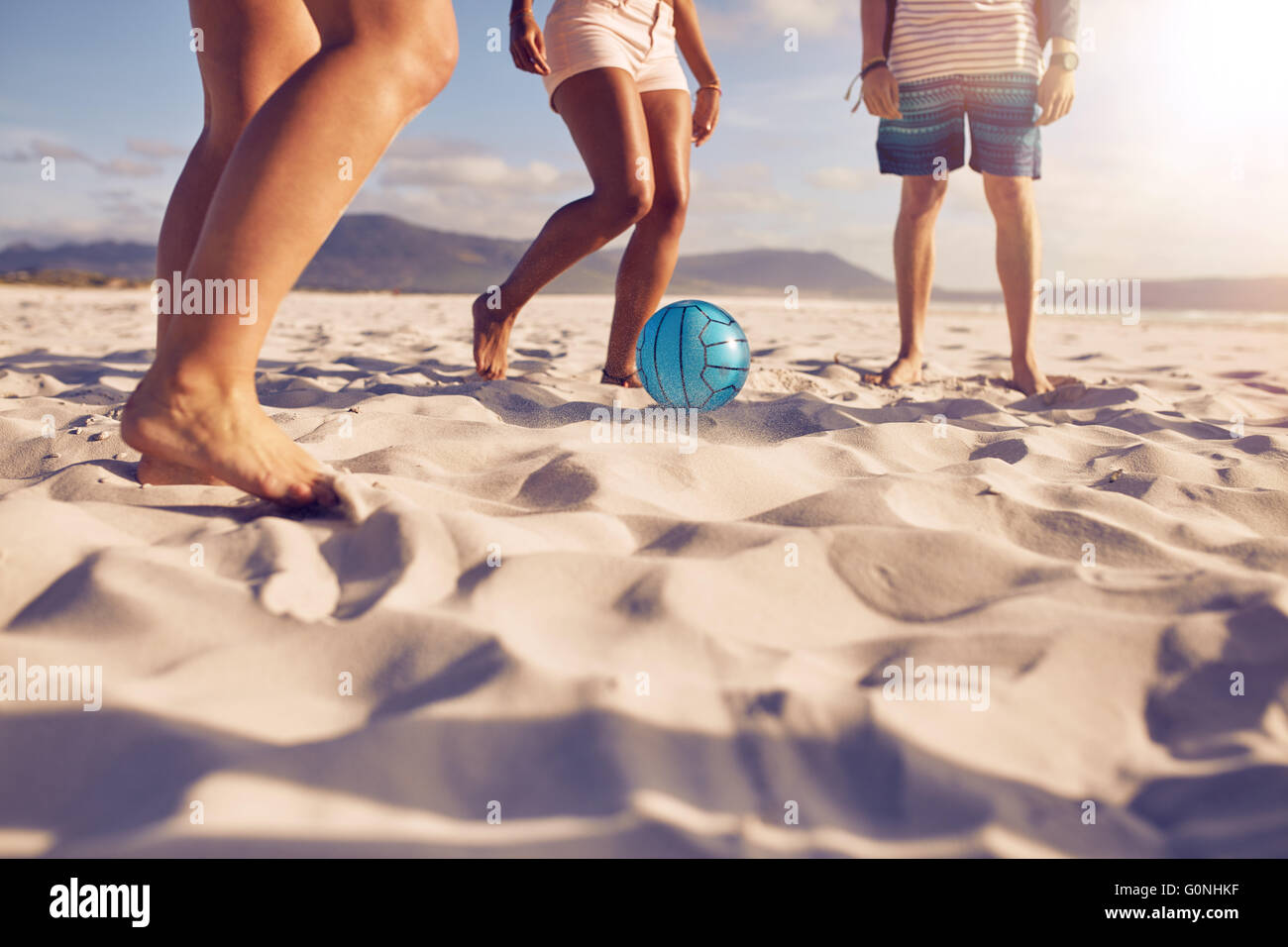 Low section portrait of group of friends playing soccer on the beach. a girl is passing the ball to friends. - Stock Image