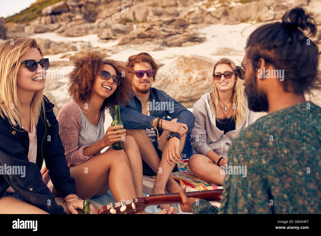 Group of young people listening to a friend playing guitar at the beach. Diverse group of friends hanging out at - Stock Image