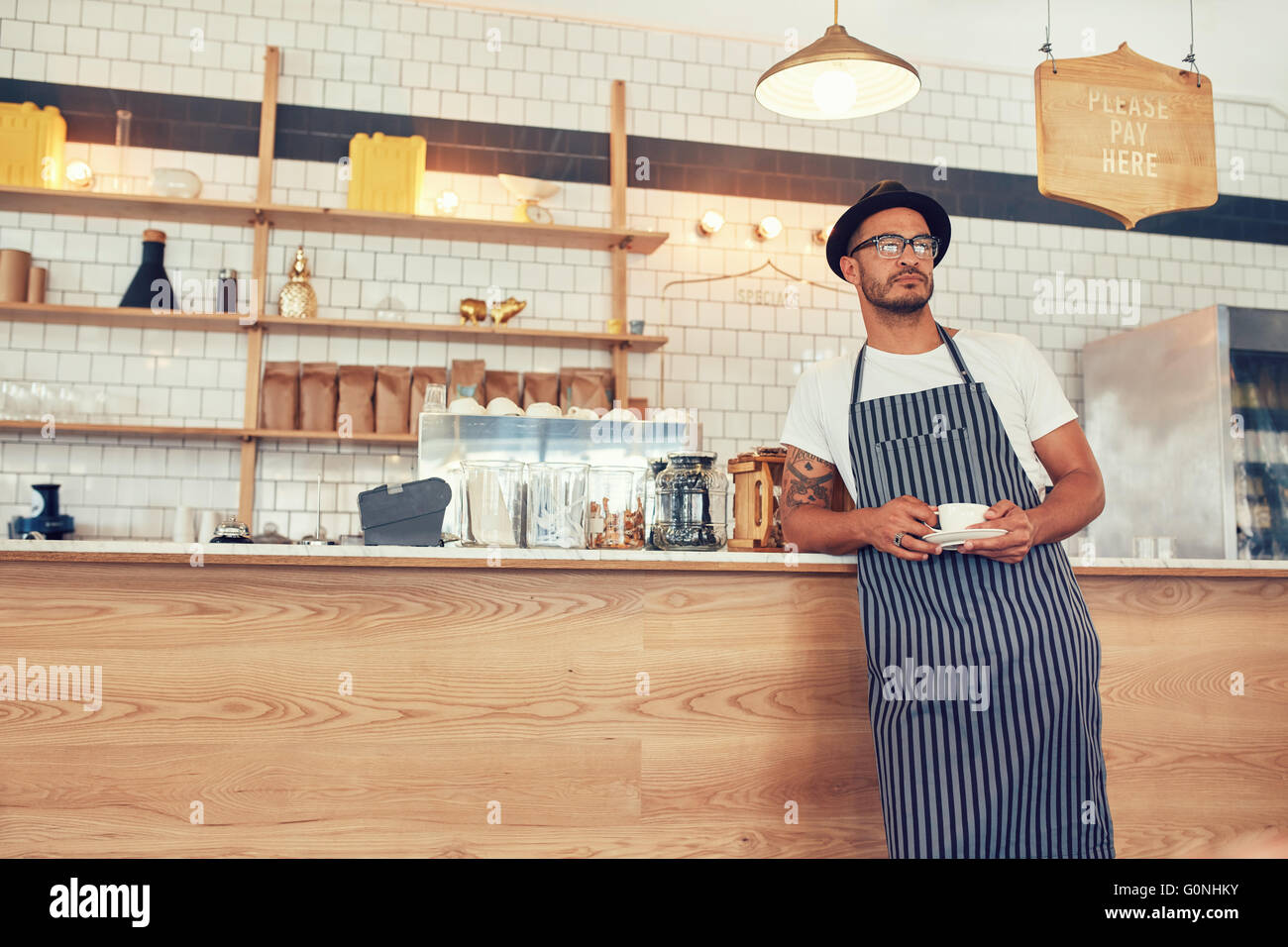 Portrait of young man working at a restaurant wearing an apron and hat leaning to the bar counter. Cafe owner standing - Stock Image