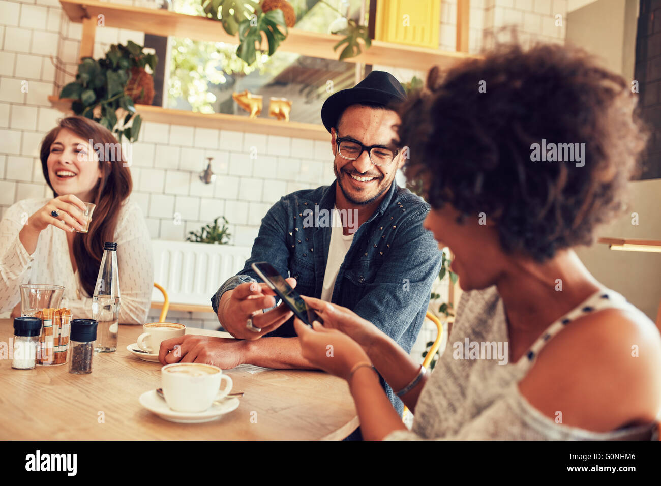 Portrait of young friends talking in cafe and looking at the photos on smart phone. Happy young people having a - Stock Image