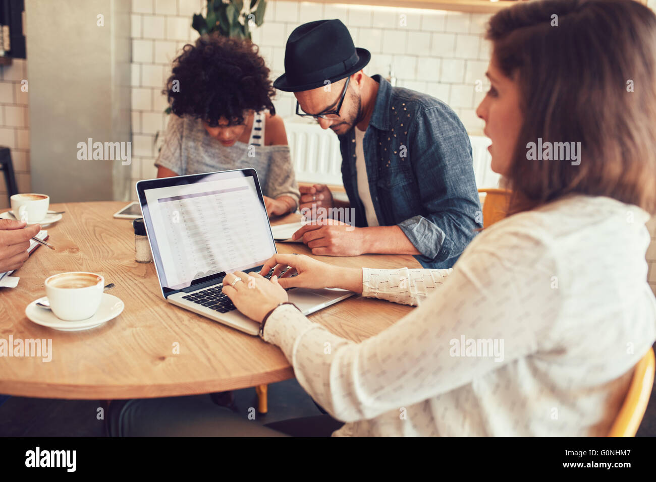 Portrait of young woman working on laptop with her friends sitting by at a coffee shop. Friends sitting around a - Stock Image